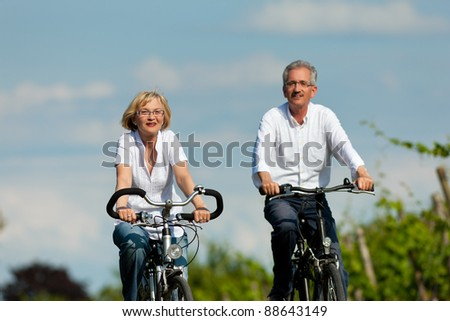 Happy mature couple - senior people (man and woman) already retired - cycling in summer in nature
