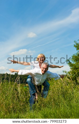 Happy mature couple - senior people (man and woman) already retired - having fun in summer in nature