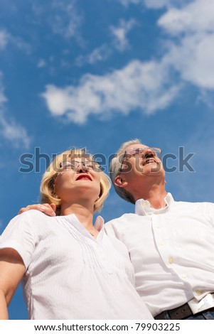 Happy mature couple - senior people, man and woman, already retired - looking to the blue sky in summer feeling free