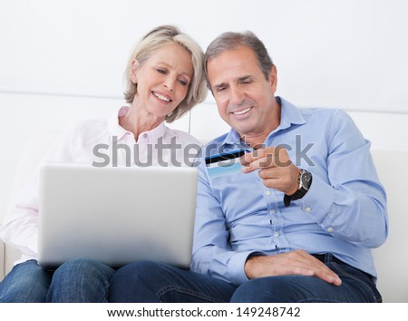 Happy Mature Couple Shopping Online On Laptop At Home