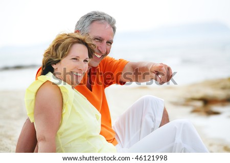 Happy mature couple sitting on the beach.