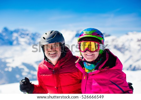 Happy mature couple skiing in the Alps mountains. Senior man and woman enjoying ski vacation in alpine resort. Active retirement. Healthy winter sport for every age.