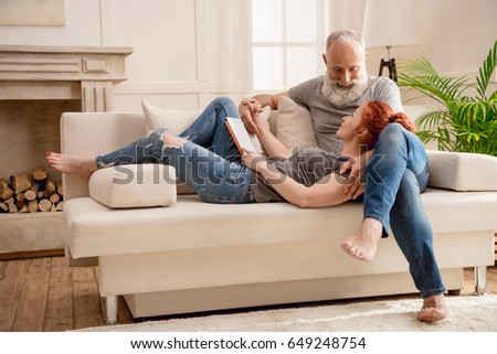 Happy mature couple using digital tablet together at home
