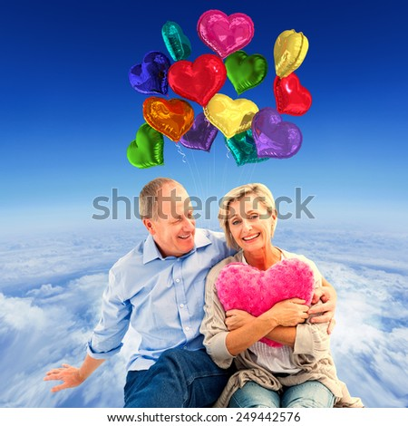 Happy mature couple with heart pillow against mountain peak through the clouds