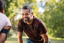 Happy mature fitness couple resting after a run in park. Smiling middle eastern man taking a break while looking at woman outdoor. Portrait of happy indian sportsman resting after jogging at park.