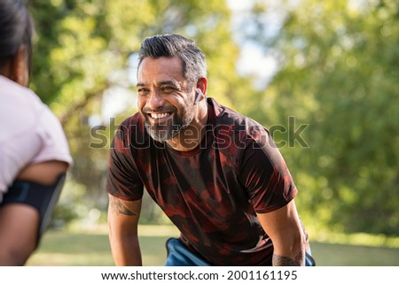 Happy mature fitness couple resting after a run in park. Smiling middle eastern man taking a break while looking at woman outdoor. Portrait of happy indian sportsman resting after jogging at park. Foto stock ©