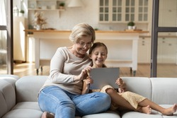 Happy mature grandmother with adorable little granddaughter using tablet relaxing on couch at home together, excited middle aged woman and cute kid looking at device screen, watching funny video