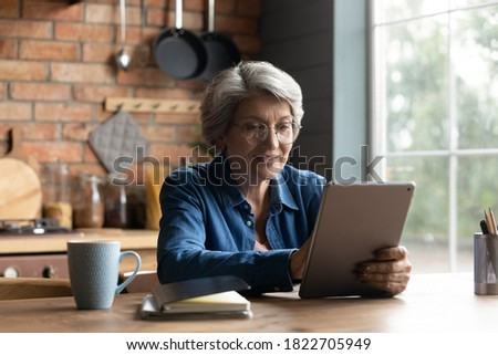 Happy mature grey-haired woman in glasses sit table at home kitchen browse internet on pad gadget. Modern smiling senior Caucasian 60s grandmother use tablet read news. Elderly and technology concept.