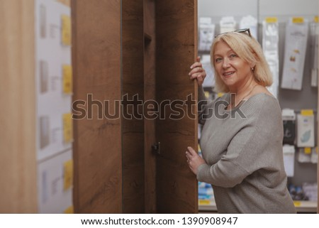 Happy mature housewife shopping for furniture, copy space. Lovely mid-aged female customer enjoying choosing new wardrobe at furnishings shop #1390908947