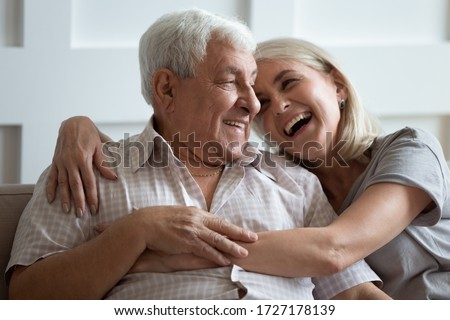 Happy mature husband and wife sit rest on couch at home hugging and cuddling, show care affection, smiling senior loving couple relax on sofa have fun, enjoy tender romantic family weekend together