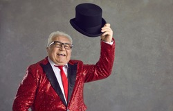 Happy mature man in glasses and fancy sequin jacket says hello and takes off black top hat. Funny elderly wedding toastmaster, conjurer, illusionist, announcer, showman or presenter greeting audience