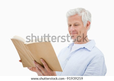 Happy mature man reading a book against a white background