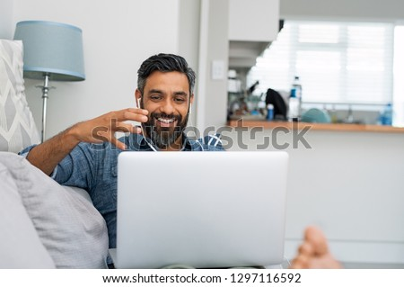 Happy mature man relaxing on couch while video calling using laptop at home. Latin man sitting on sofa and making a video call. Smiling middle eastern businessman doing online video.