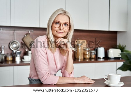 Happy mature middle aged 50s woman wearing glasses sitting at the kitchen table. Smiling older adult elegant blond lady looking at camera posing at home drinking coffee. Portrait. Stok fotoğraf ©