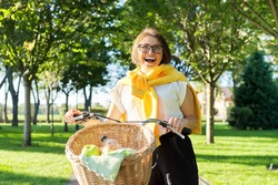 Happy mature middle aged woman with bike with basket in park on sunny day. Age, active healthy lifestyle, joy and happiness of older people