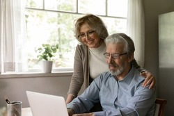 Happy mature OAP couple study internet app on laptop, grandparents use computer at home for online shopping. Smiling middle aged pensioner wife hugs senior husband during video call to relations