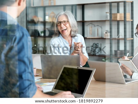 Happy mature old female mentor coach supervisor training young interns at group office meeting professional workshop. Cheerful middle aged teacher professor laughing with students at university class.