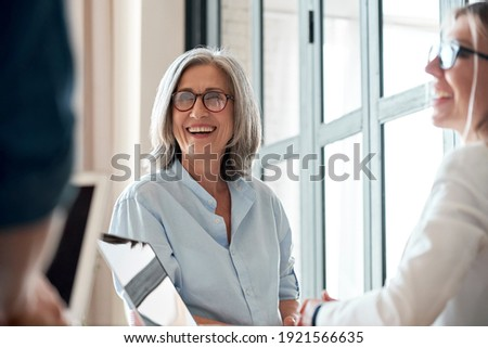 Happy mature old female mentor coach supervisor training young interns at group office meeting professional workshop. Smiling middle aged teacher professor laughing with students at university class