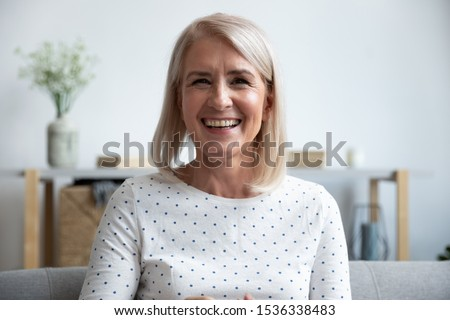 Happy mature old woman blogger looking at camera at home, smiling middle aged senior lady sit on sofa talking by webcam laughing enjoying video conference call online or shooting blog vlog at home