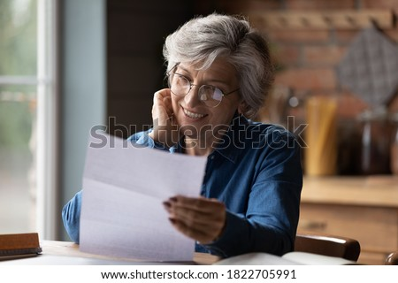 Happy mature 60s woman in glasses sit at table manage paperwork read postal letter correspondence. Smiling elderly Caucasian female in spectacles consider post document or bank paper notice.