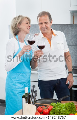 Happy Mature Toasting Glass Of Wine In Kitchen