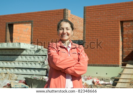 Happy  mature woman  against  construction work