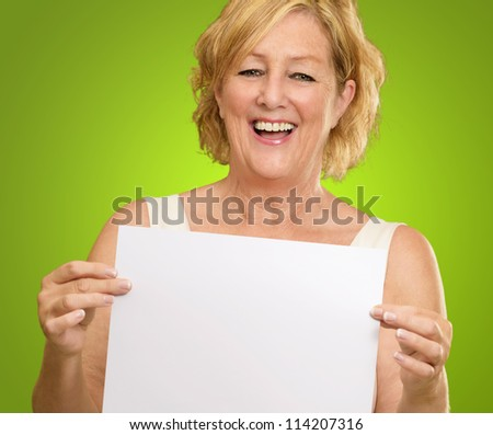 Happy Mature Woman Holding A Blank Paper On Green Background