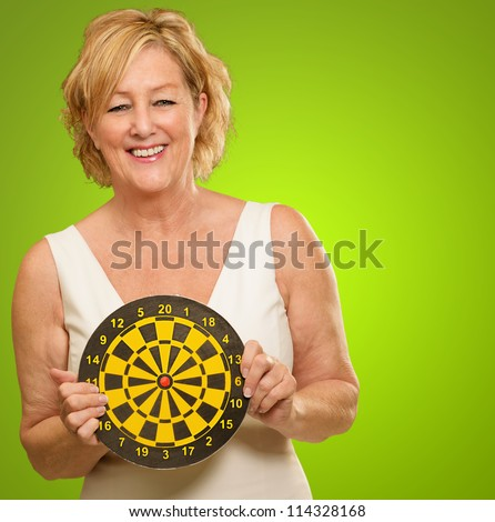 Happy Mature Woman Holding Dartboard On Green Background