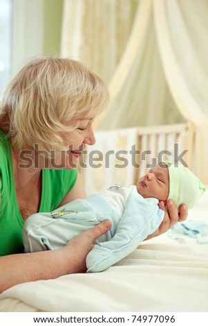 Happy mature woman holding her newborn grandson