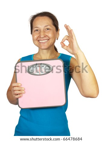Happy mature woman holding scale .Isolated on white