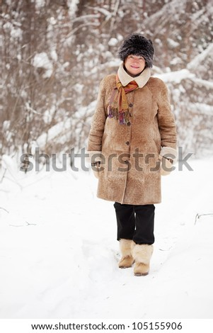 Happy mature woman is walking at winter park
