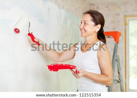 Happy mature woman makes repairs at home