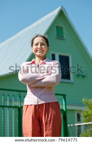 Happy mature woman posing in front of her  home
