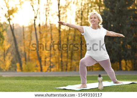 Happy mature woman practicing yoga in park. Active lifestyle