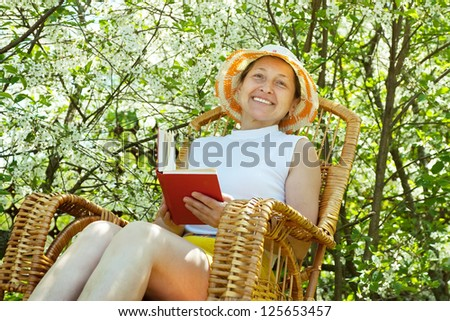 Happy mature woman relaxing in bloom garden