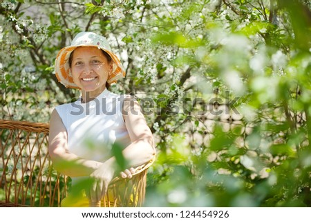 Happy mature woman relaxing in blossoming garden