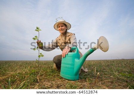 Happy mature woman, watering can and growing plant at spring field