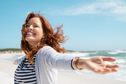 Happy mature woman with arms outstretched feeling the breeze at beach. Beautiful middle aged woman with arms up dancing on beach. Mid lady feeling good and enjoying freedom at sea, copy space.