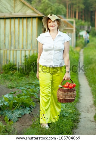 Happy mature woman with basket of harvested vegetables