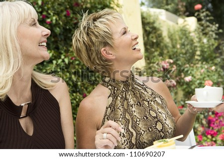 Happy mature woman with female friend holding coffee cup
