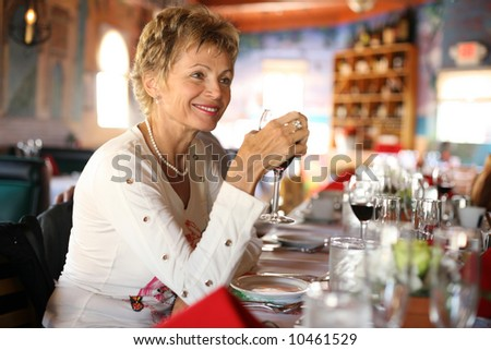 stock photo : Happy mature woman with glass of wine in a restaurant at party