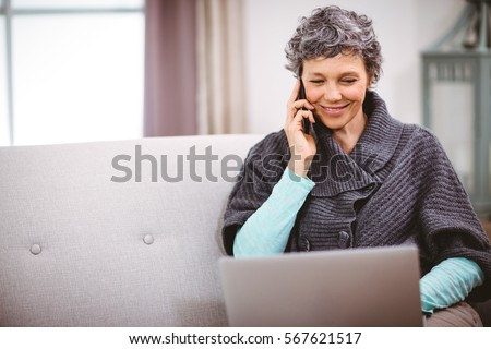 Happy mature woman with laptop using mobile phone while sitting on sofa at home. Working from home in quarantine lockdown. Social distancing Self Isolation
