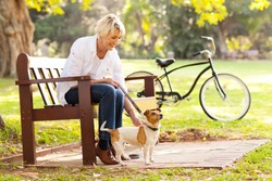happy mature woman with pet dog outdoors