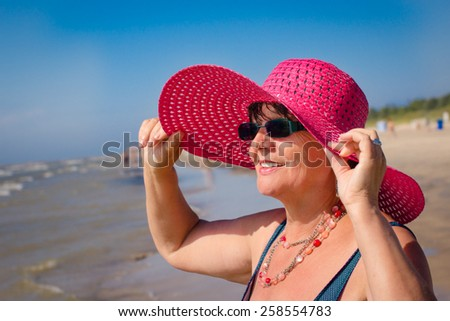 Happy mature woman with pink hat on the beach. Selective focus.