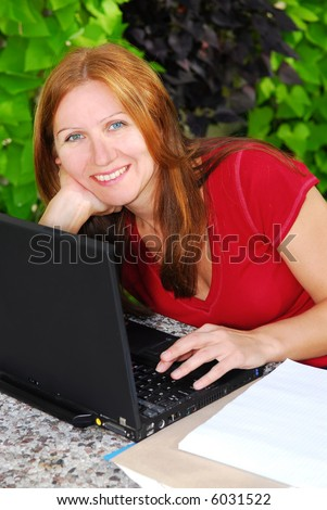 Happy mature woman working on portable computer at home, small business owner