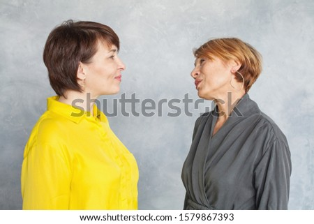 Happy mature women chatting and looking each other and on gray background. Two ladies 45 and 60 years old portrait