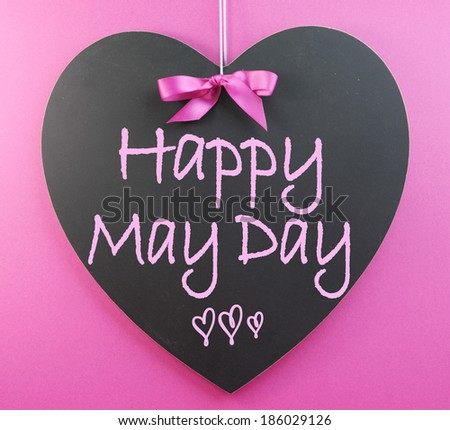 Happy May Day handwriting greeting on heart shaped blackboard for 1st First of May celebrations on pink background.