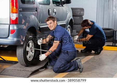 Happy Mechanic Fixing Car Tire At Repair Shop