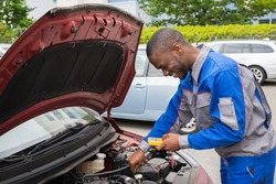 Happy Mechanic Using Multimeter To Check The Voltage Level In A Car Battery