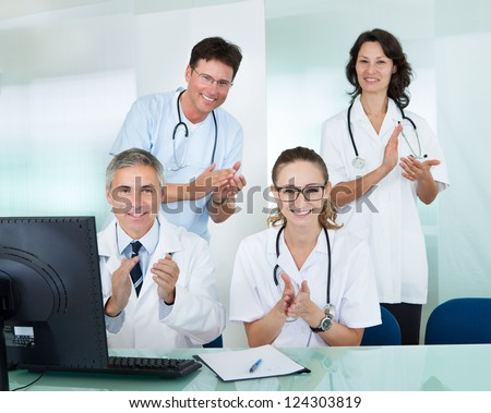 Happy medical team comprising male and female doctors smiling broadly and giving a thumbs up of success and hope